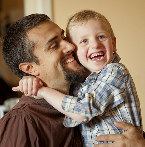"""Young boy laughing and hugging smiling father"""
