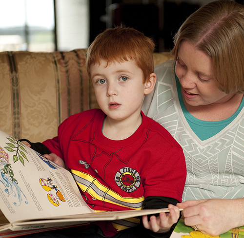 """Mother reads book to young boy"""