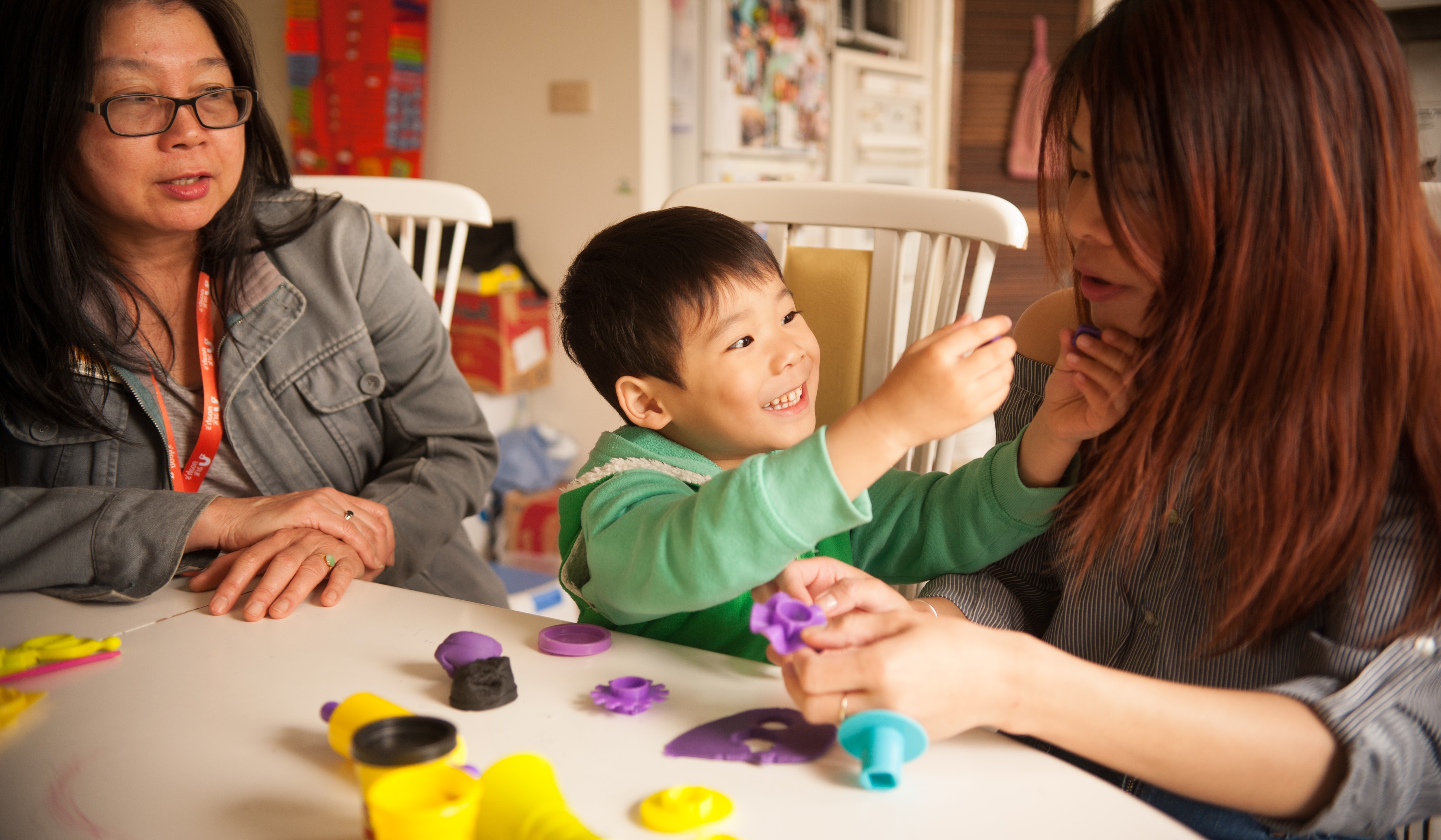Young boy plays with his mum and therapist at the table