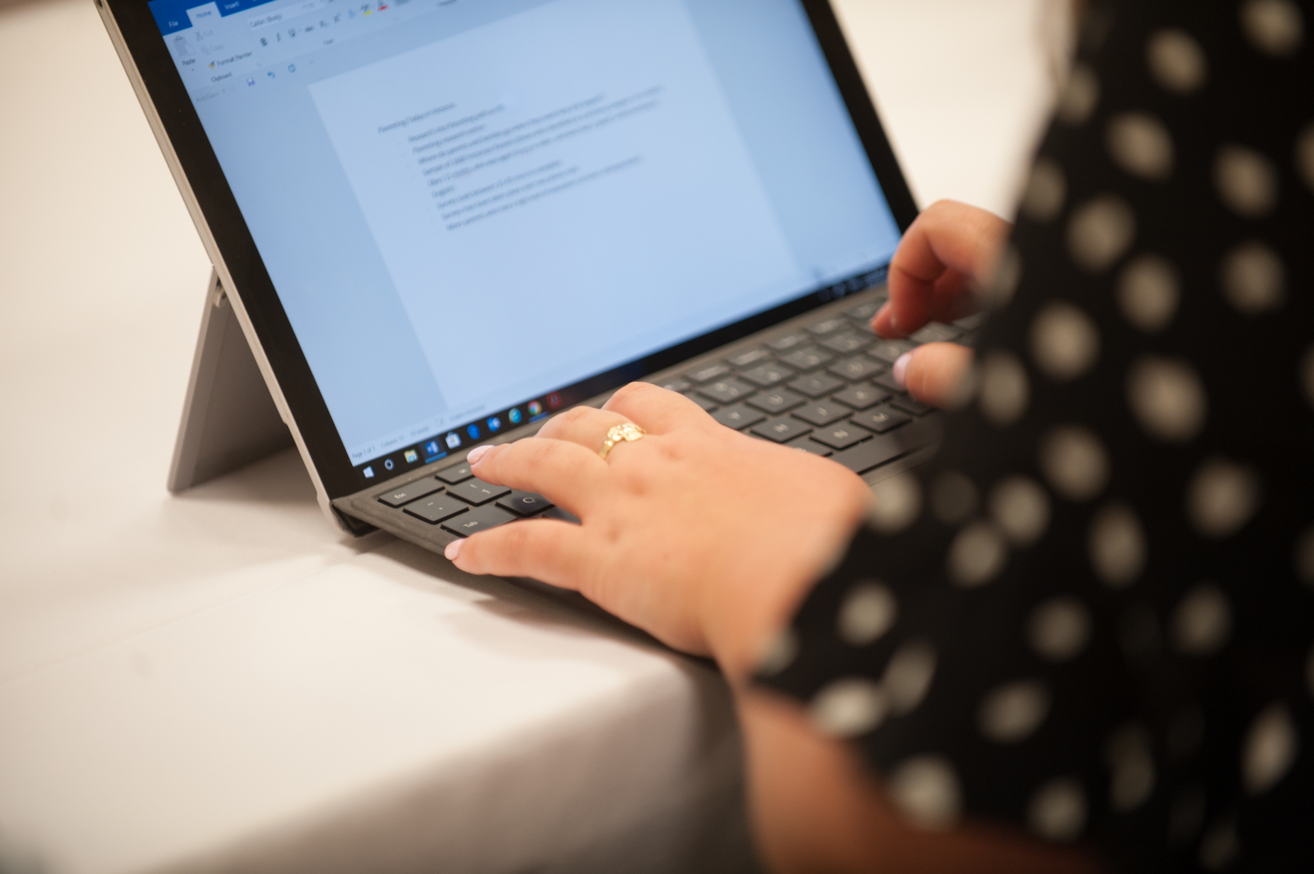 Close up of a lady's hands typing on a laptop