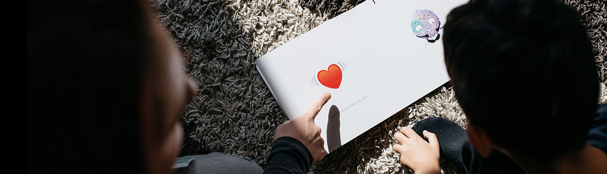 A close up of an open book with a love heart drawing